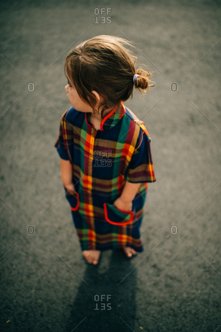 Little girl standing with hands in pockets of her plaid dress