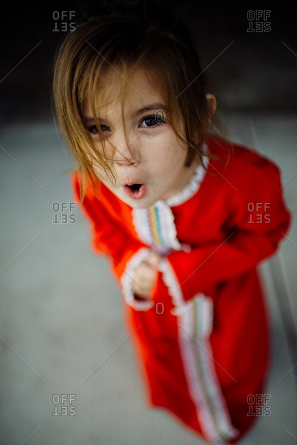 Little girl wearing red dress making a silly expression