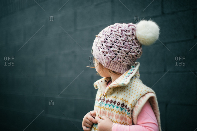 Little girl wearing a knit hat and vest looking away