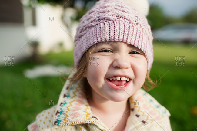 Little girl wearing a knit hat and vest smiling