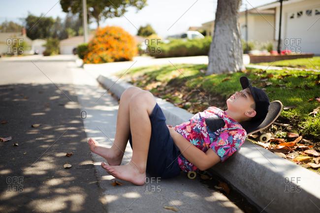 Boy resting on a skateboard on curb