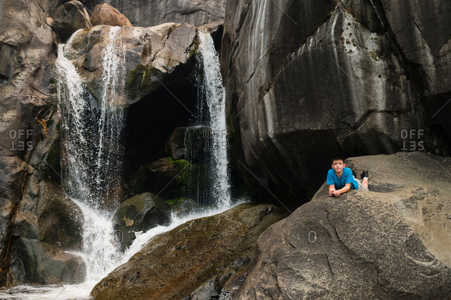 Boy lying on rock by waterfall