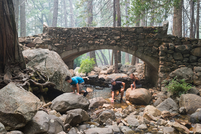 Father and kids exploring a rocky river under a bridge