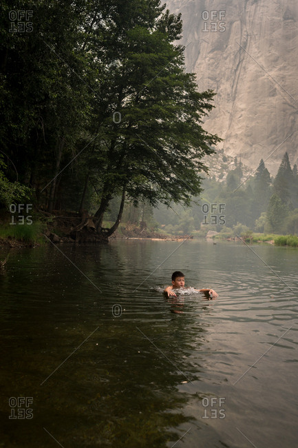 Boy swimming in a mountainside lake