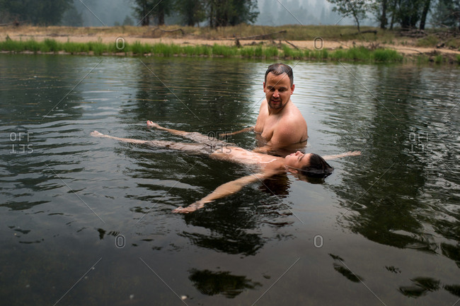 Father teaching boy to float in a lake