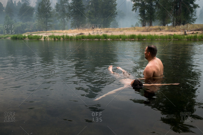 Son floating by father in a lake