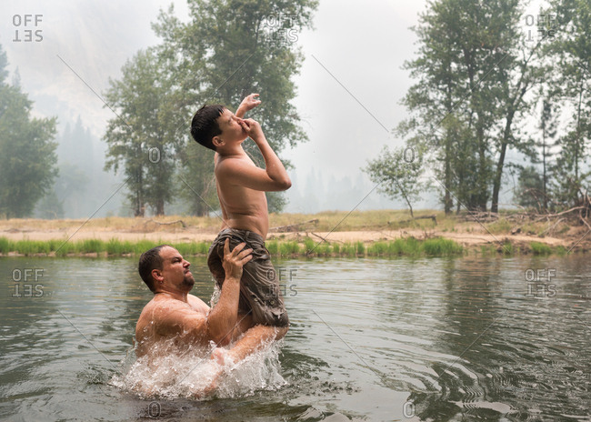 Father tossing son in a lake