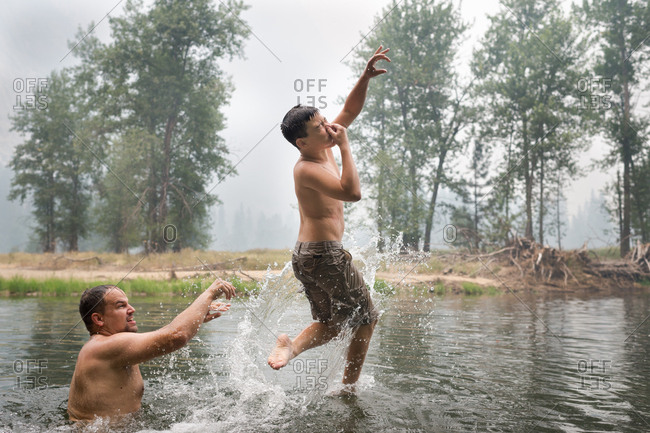 Father throwing son in a lake
