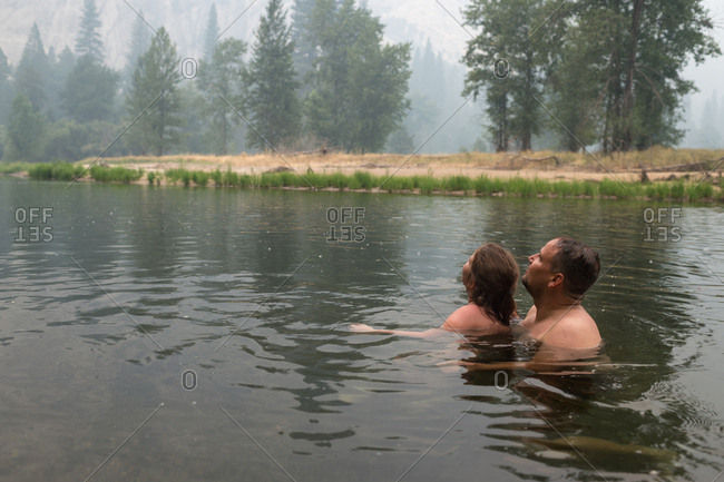 Father and daughter swimming in a lake during the rain