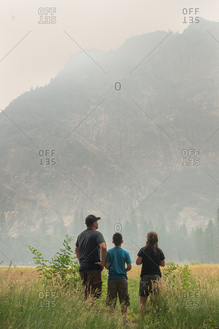 Father and kids looking at a mountain