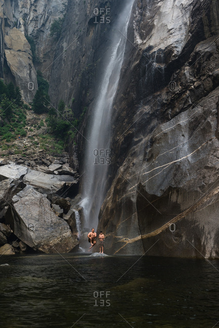 Father and son jumping into lake at bottom of waterfall