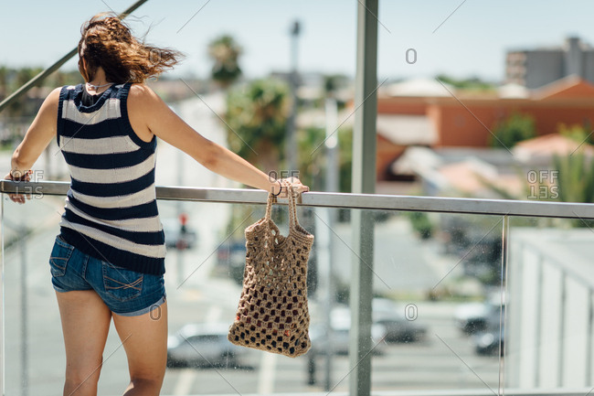 Rear view of woman looking over railing