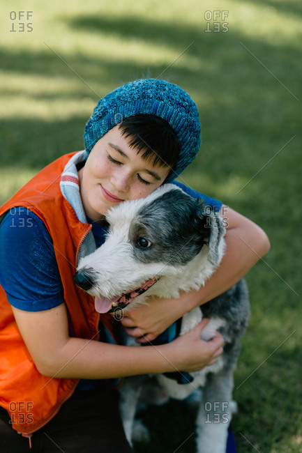 Boy smiling while hugging his dog