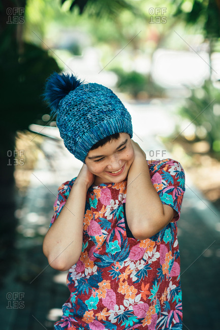 Portrait of a young boy wearing a blue knit hat and floral shirt