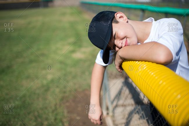 Young boy leaning over edge of fence