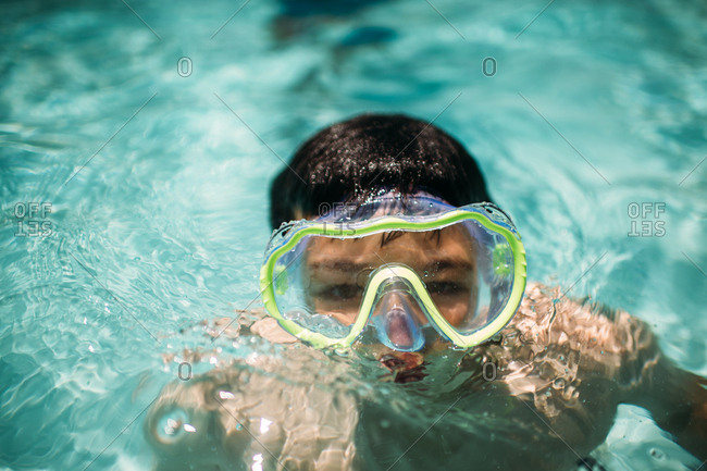 Boy swimming in a pool wearing goggles
