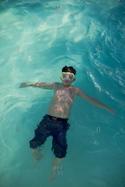 Boy floating in a pool wearing goggles