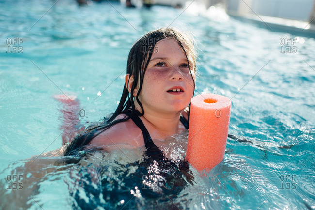 Girl swimming with orange noodle in a pool