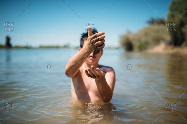 Boy playing with mud in a lake