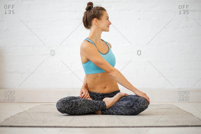 Woman twisting her body while sitting in yoga pose