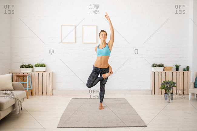 Young woman doing standing yoga stretches at home