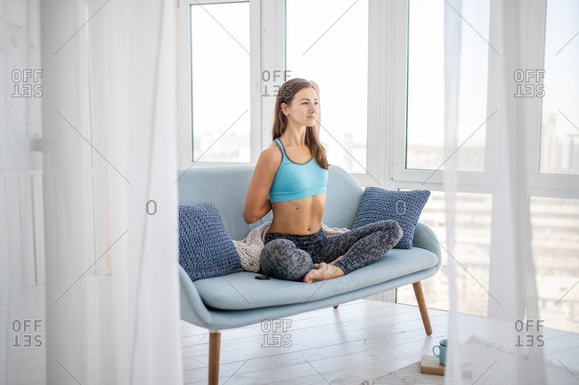 Woman doing yoga stretches on sofa
