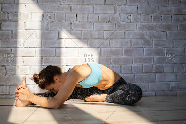 Woman stretching in front of brick wall