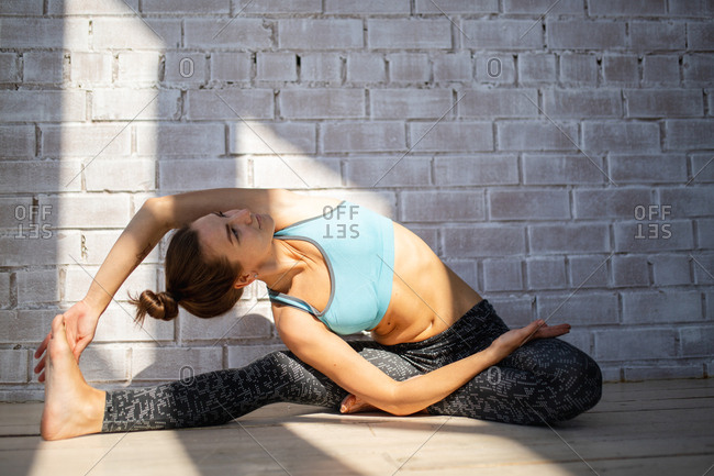 Young woman stretching in front of brick wall
