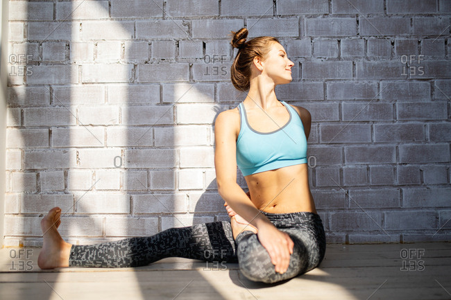Young woman stretching in front of a white brick wall
