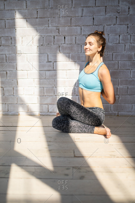 Woman stretching in front of a white brick wall