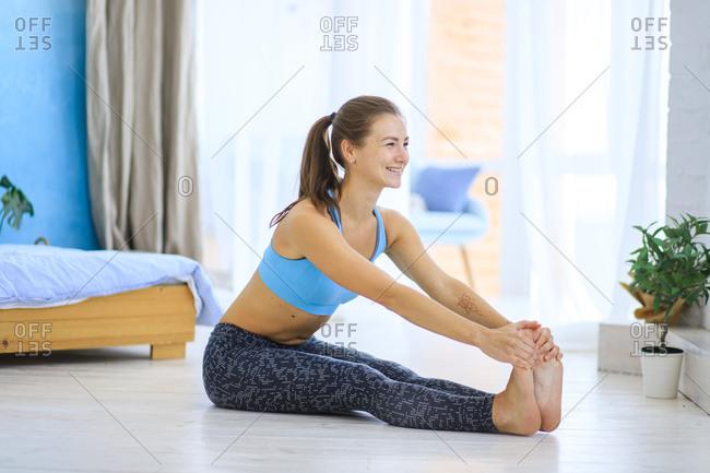 Happy woman stretching on bedroom floor