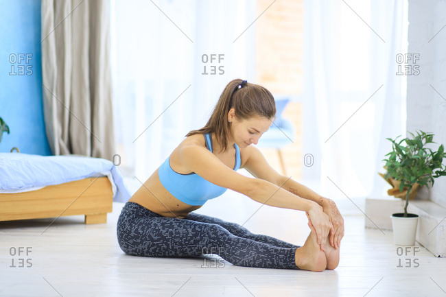 Young woman stretching on floor