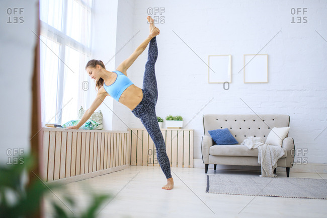 Young woman practicing yoga in her living room