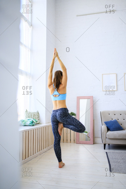 Rear view of woman practicing yoga tree pose in her living room