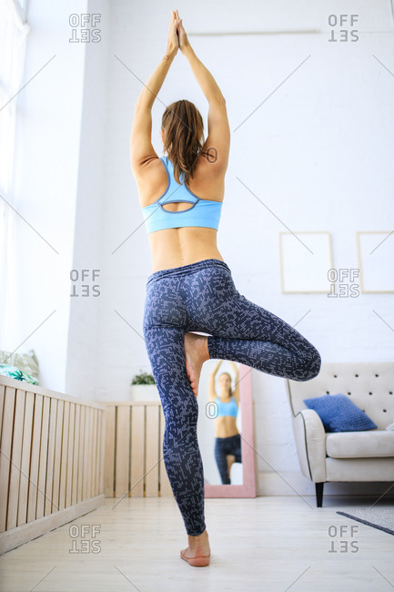 Back view of woman practicing yoga tree pose in her living room