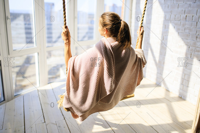 Rear view of woman on indoor swing looking out window