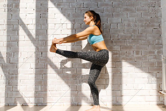 Woman stretching legs in front of brick wall