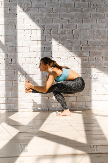Young woman doing yoga pose in front of brick wall