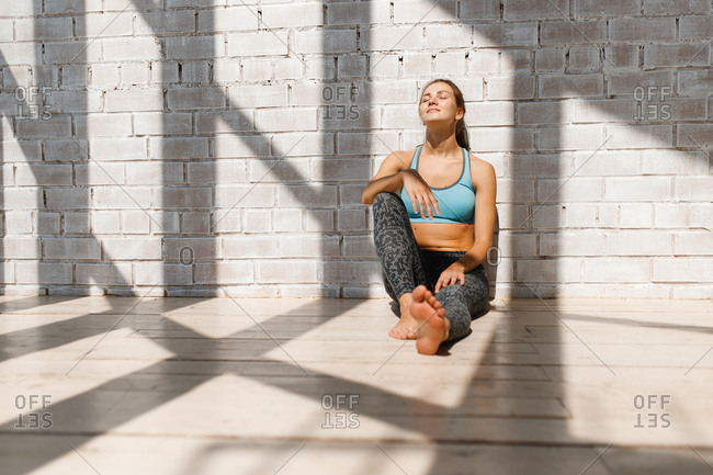 Young woman soaking up sunlight while resting during yoga workout