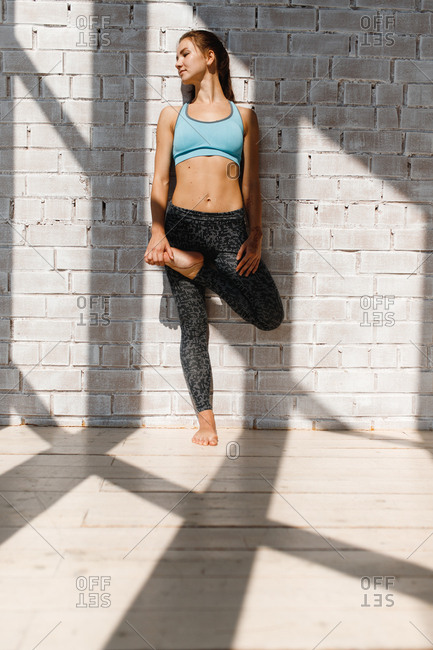 Young woman standing in sunlight while doing yoga workout