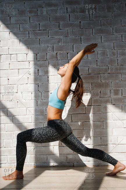 Woman doing warrior yoga pose in front of brick wall