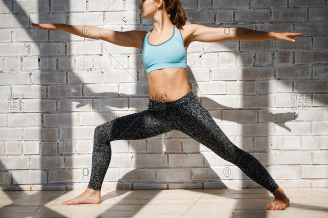 Woman doing warrior 2 yoga pose in front of brick wall