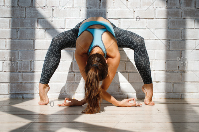 Young woman practicing yoga in front of brick wall