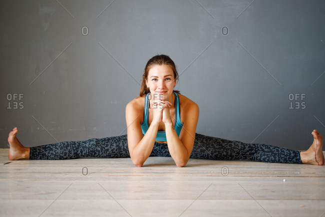 Happy young woman stretching on floor