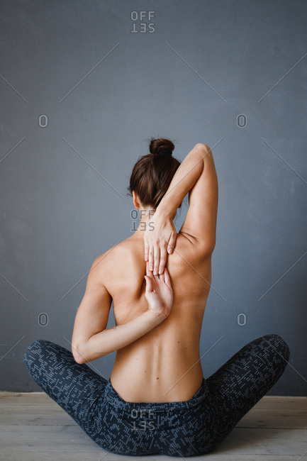 Rear view of topless woman doing yoga stretches