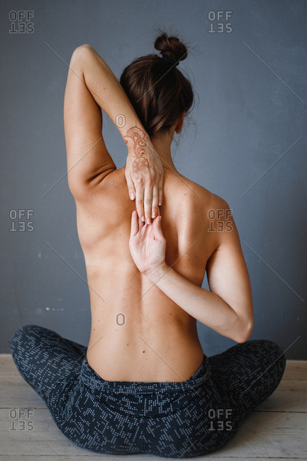 Back view of topless woman doing yoga stretches