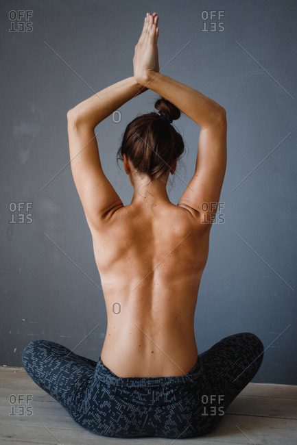 Topless woman doing yoga stretches from behind