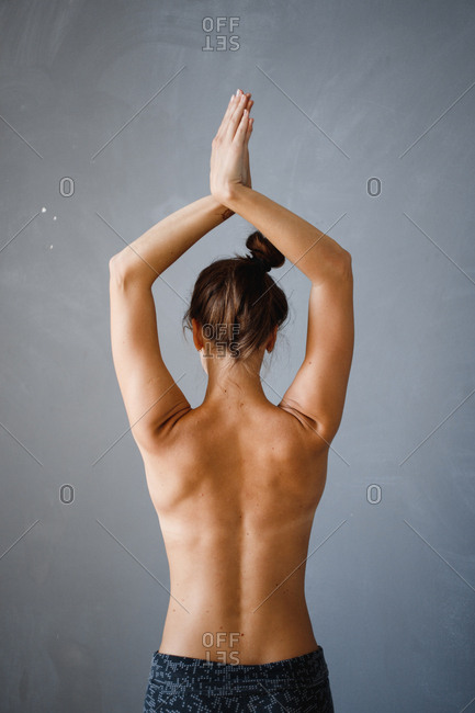 Nude woman doing yoga stretches from behind