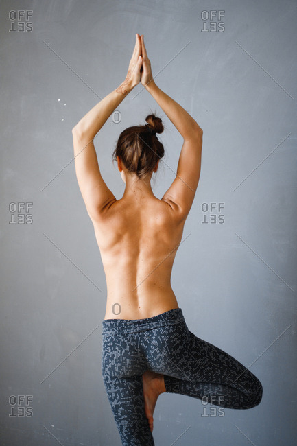 Rear view of topless woman doing yoga tree pose