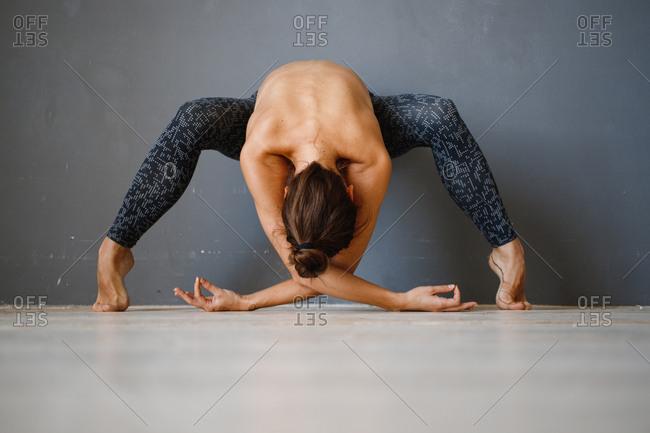 Topless woman doing yoga pose